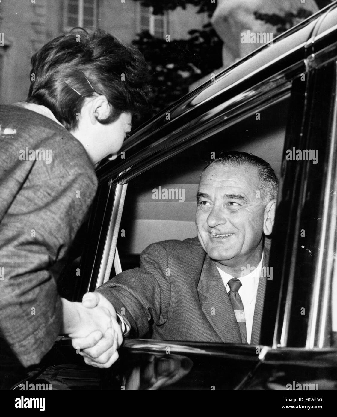 President Johnson greets civilian from car - Stock Image