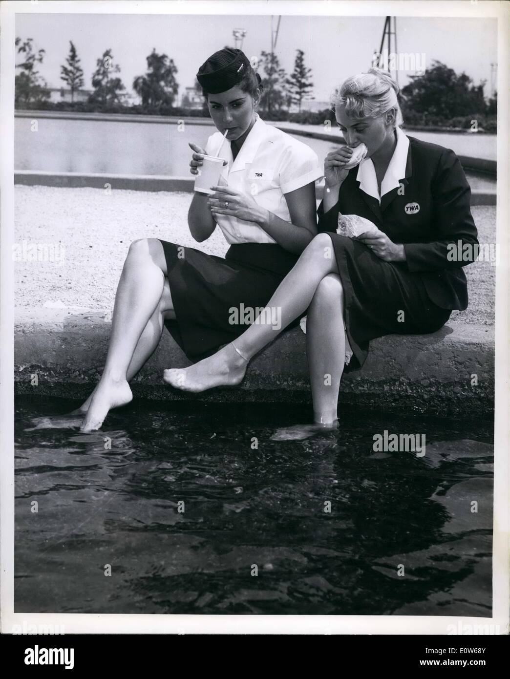 Aug. 08, 1961 - While the eastern seaboard sweltered beneath the August heat wave TWA ground hostesses Helen Cooper (left) and Gail Clayton enjoyed outdoor air conditioning as they lunched in the cooling promimity of the beautiful airport fountains. - Stock Image