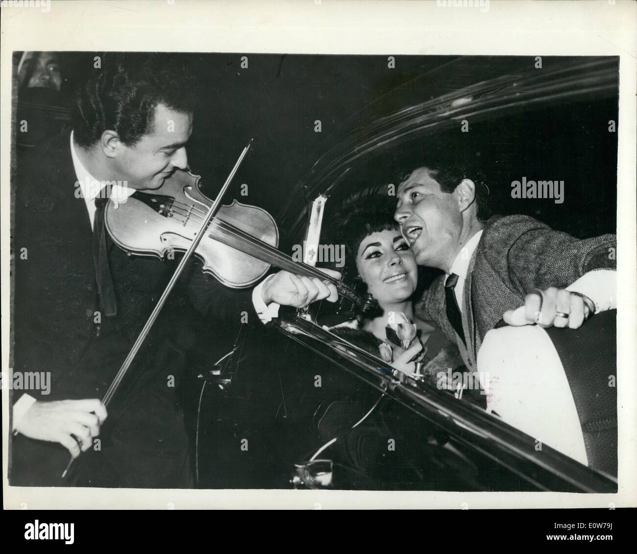 Oct. 10, 1961 - Eddie Fisher Serenades Liz Taylor in Rome with Help of a Violinist. Eddie Fisher sand a serenade to his wife, actress Elizabeth Taylor, now in Rome for the filming of Cleopatra, recently as they were driving back from a restaurant in the Via Veneto, as he spotted a street violinist who helped to land the right atmosphere. Photo Shows: Fisher singing to Taylor, seated in their car. - Stock Image