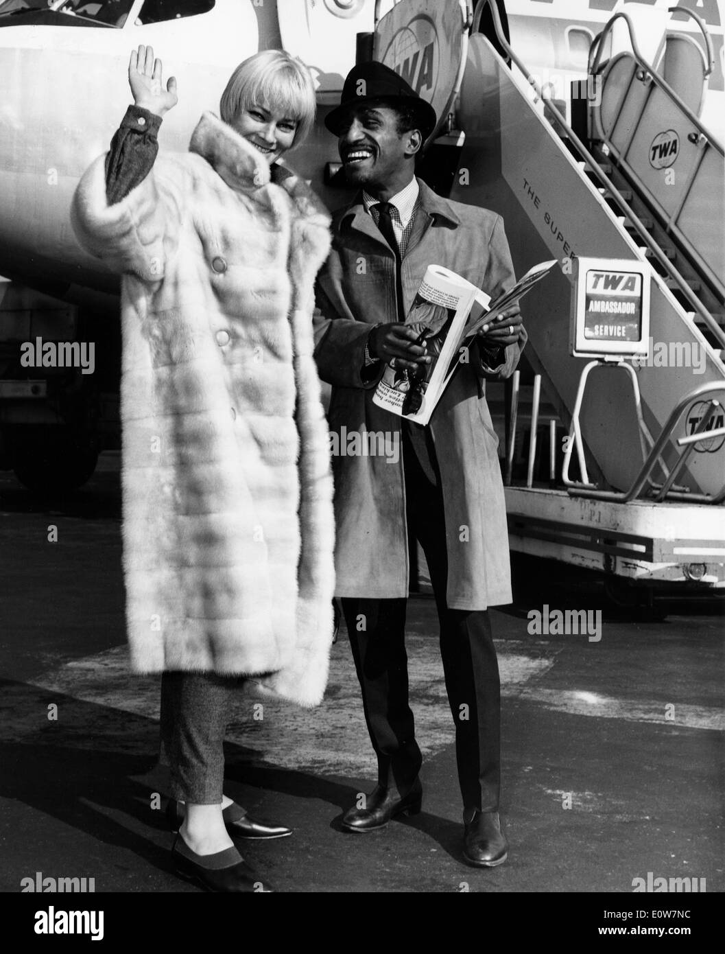 Sammy Davis Jr. boarding a plane to Los Angeles with wife May Britt - Stock Image