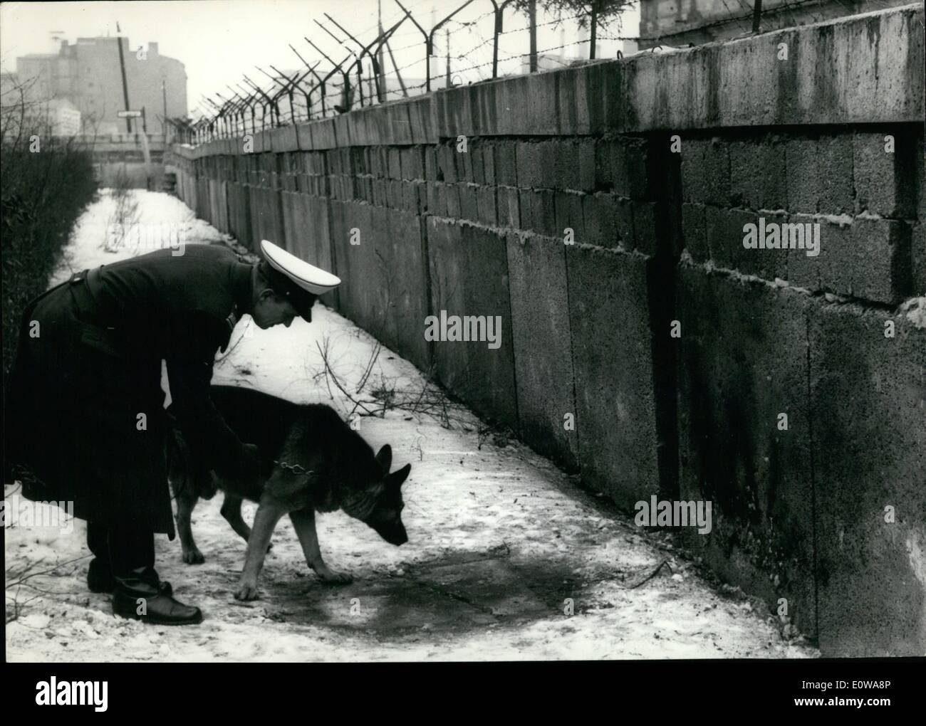 Mar. 03, 1962 - Explosives attempt against the wall in Berlin.: Today in the night unknown people has made an explosives attempt against the Communist wall in the West Berlin quarter Kreuzberg. The wall has only small hurts but a flat-house next in the windows. Photo shows a West - Berlin policeman with his service-dog inquires the place of the explosion at the communists wall. - Stock Image