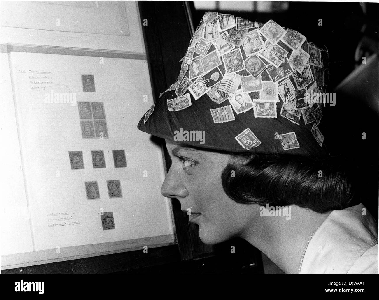 Model wearing a hat covered with a variety of postage stamps - Stock Image