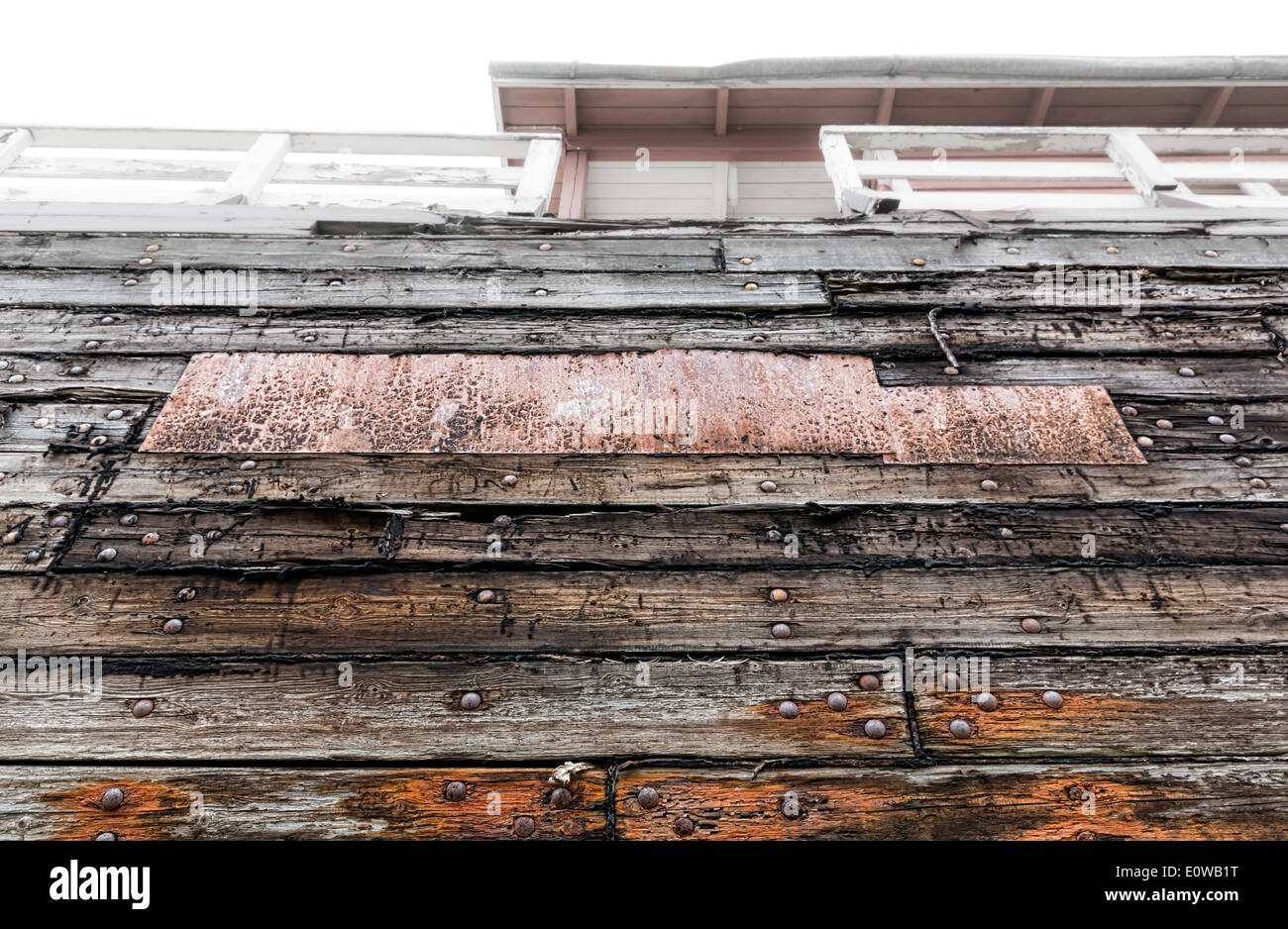 Old outer wall of a wooden boat at a shipyard - Stock Image