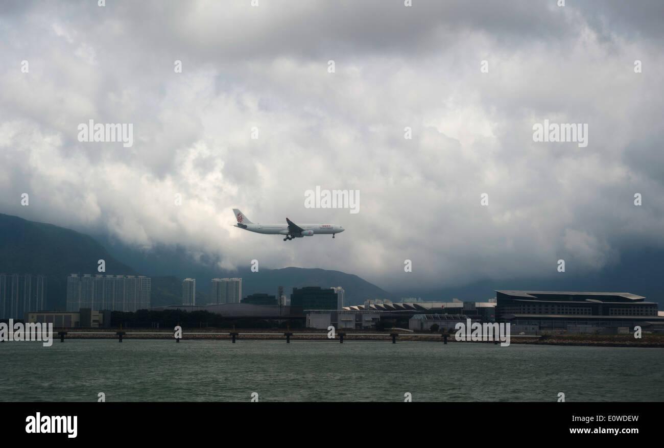 Airplane lands at Hong Kong International Airport, Chek Lap Kok island, Hong Kong, China, South East Asia in bad weather. - Stock Image