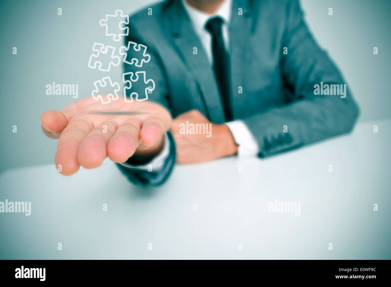 a businessman with some jigsaw puzzle pieces in his hand Stock Photo