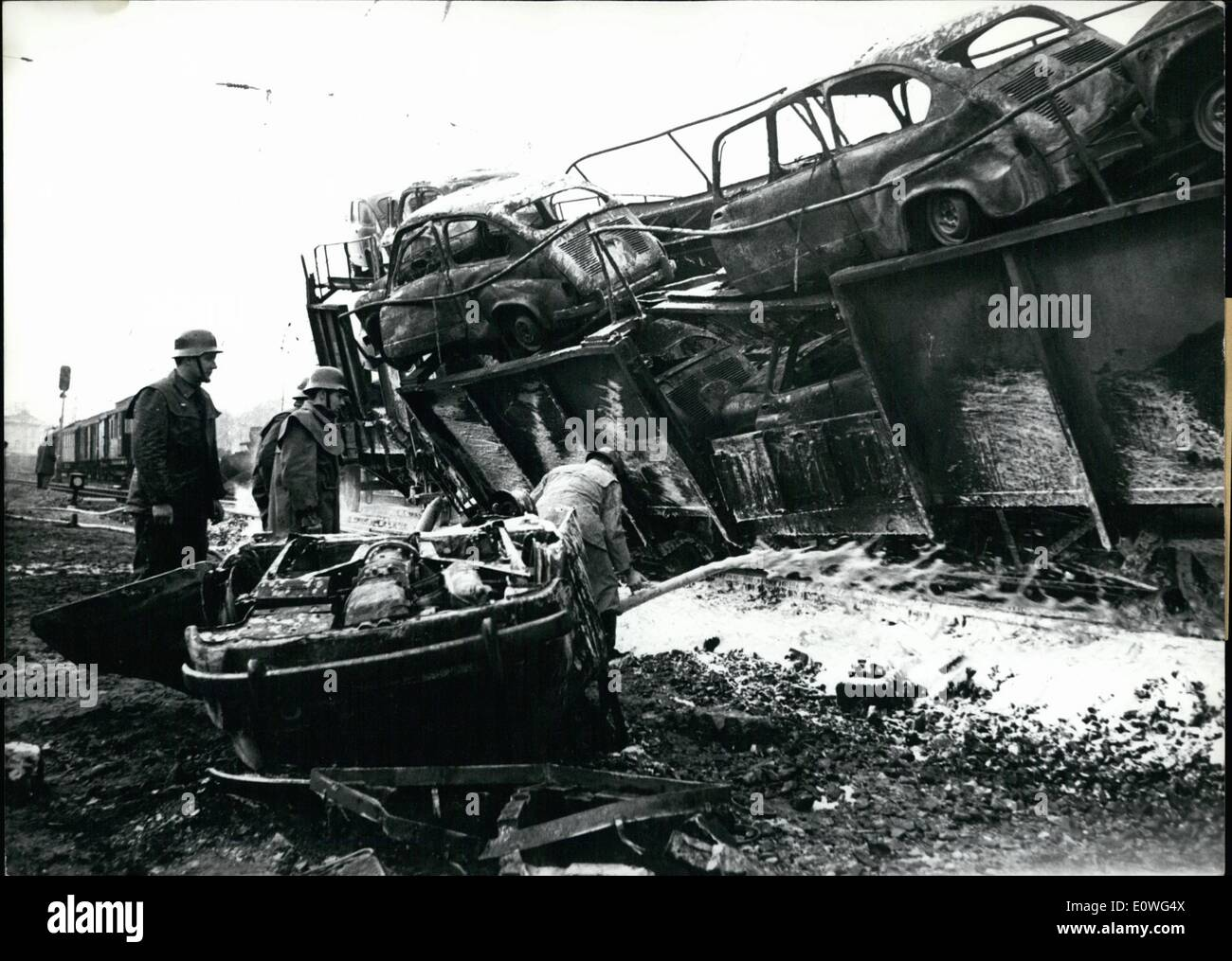 Nov. 11, 1962 - Railway accident near Munich On aga inst 2 clock in he morning 2 goods- train collided at pfaffenhoifon (Pfaffenhofen) near Munich. Most of the waggons cya -shod down a sope and burnt out,. one of the 2 trains was a transport train with motorcars coming from the factory. The damage amount to a bout 1 million Dm (Deutsche Mark) Luckely human life's have not been injured. photo shows Extinguish-work at the completely burnt out motorcars. - Stock Image
