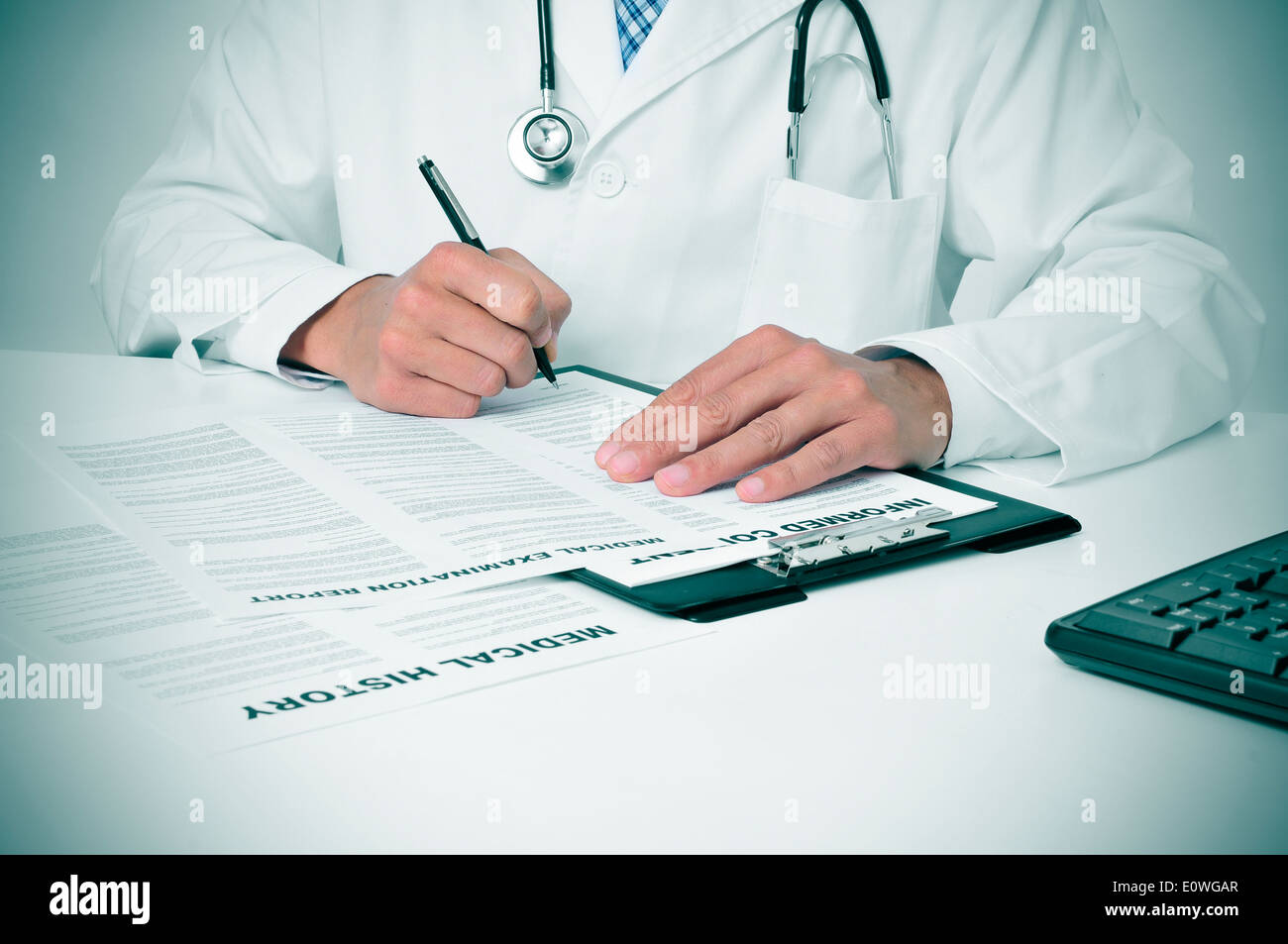 a doctor in his office checking out some documents - Stock Image