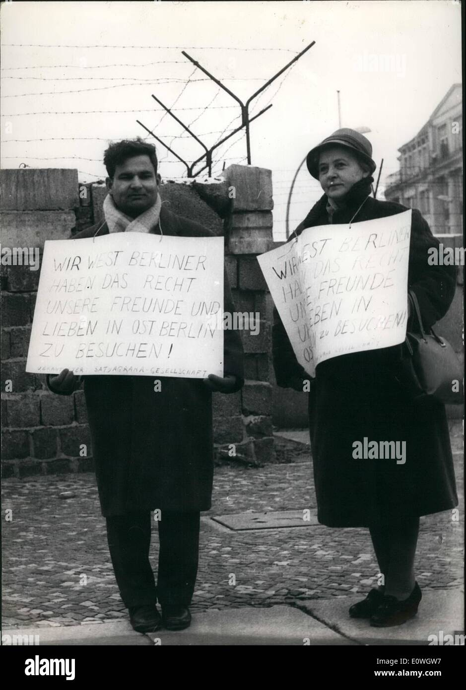 Dec. 12, 1962 - The right to see family and friends: on Wednesday (19.12) two Westberliner demonstraters stood by the wall in Chausseestrasse (Westberlin), to demonstrate against the East-Germany government line, in not letting people from the west visit friends and relations in the east. PHoto shows Nath Zutshi a chemical engineer on the left and a woman companion stand with plackards by the wall in Chausseestrassa today. Stock Photo