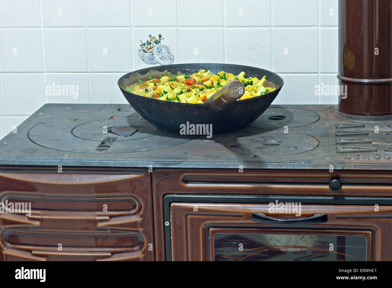 Cooking a vegetable dish on wood burning cast iron oven - Stock Image