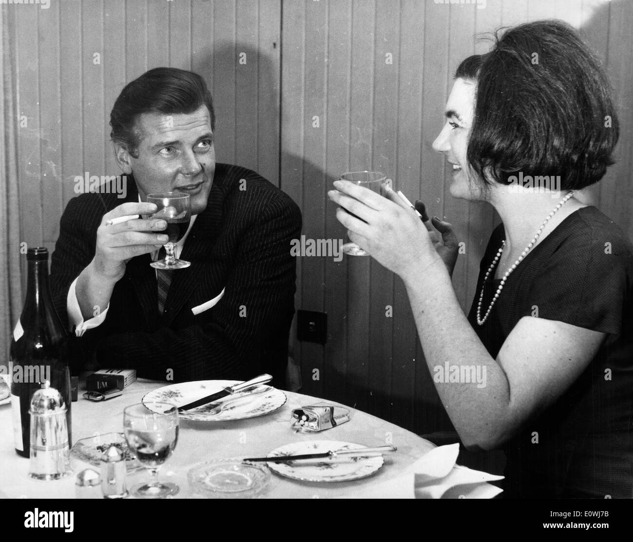 Actor Roger Moore eating dinner with journalist Jill Robetson - Stock Image