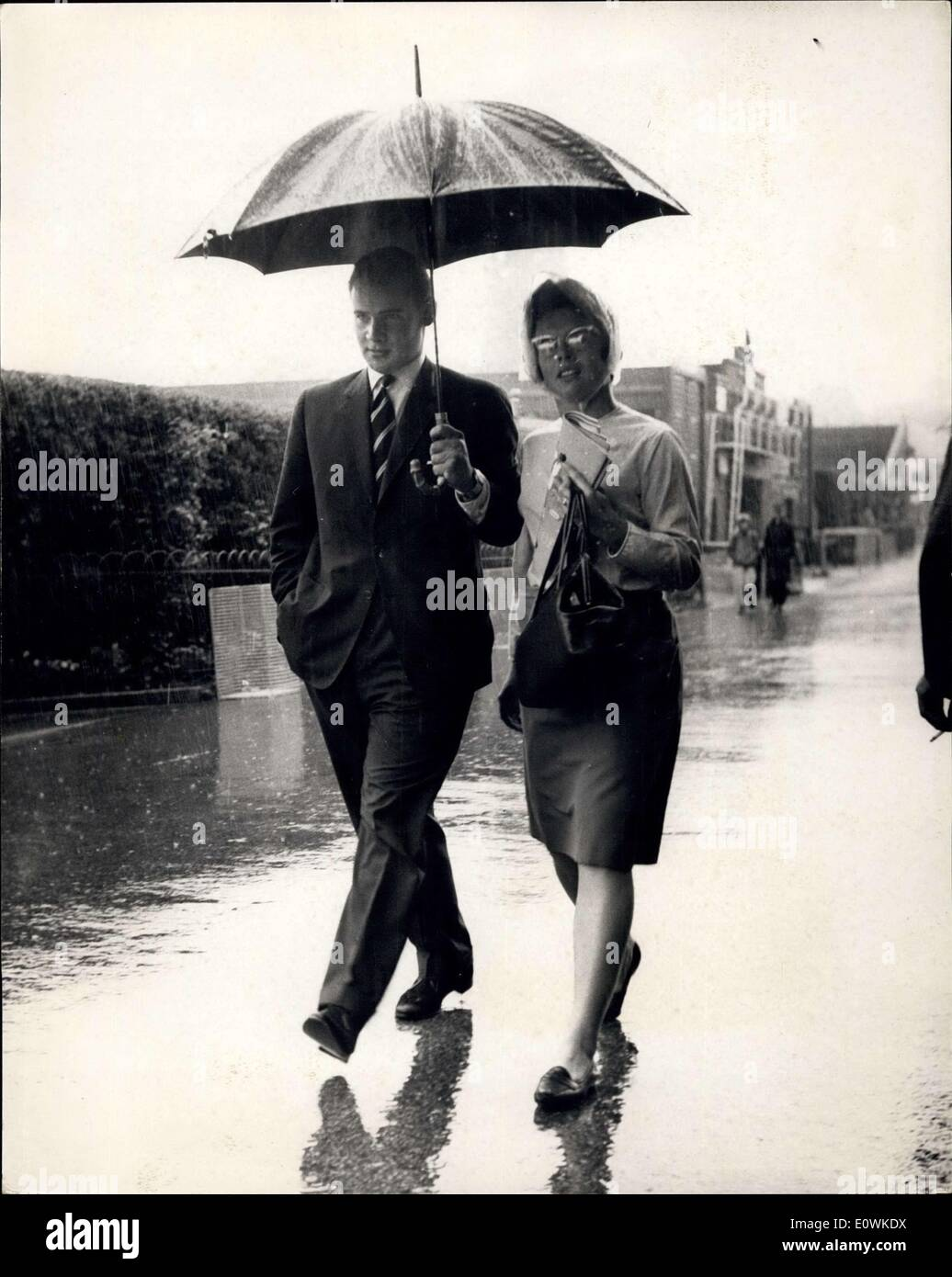 Jul. 06, 1963 - Heavy Rain Delays Play At Wimbledon: Heavy rain was delaying the start of play in the tennis tournament at Wimbledon this afternoon. Photo shows One of today's finalist Billie Jean Moffitt shares an umbrella with a friend at Wimbledon this afternoon. - Stock Image