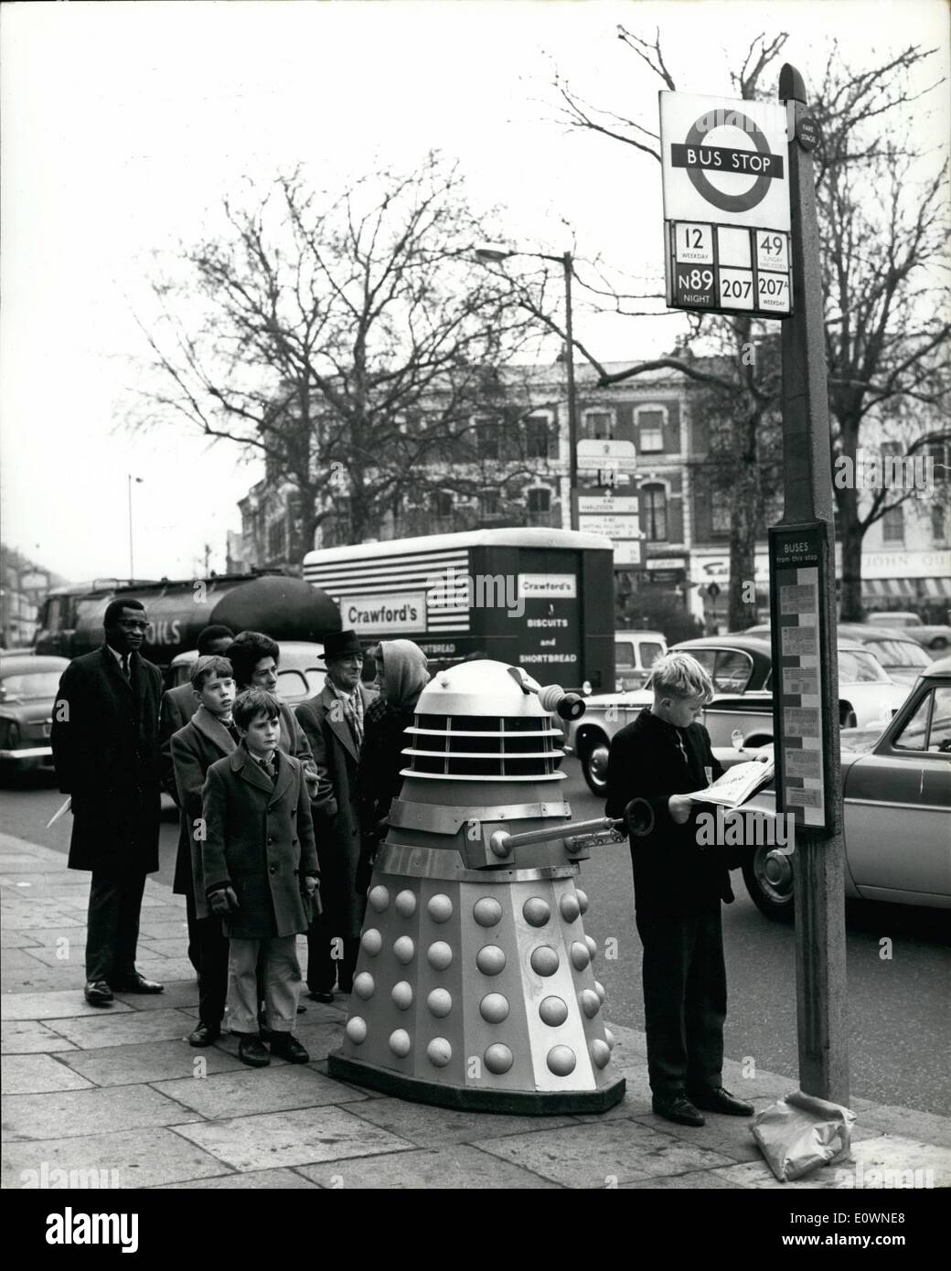 Dec. 12, 1963 - Space vehicles in Shepherd's bush.: B.B.C. Television's ''Dr. Who'' programme on Saturdays, in putting out an edition this week that features some space vehicles which are known as ''Daleks''. These vehicles seemed to have somehow got loose, and were to be seen this morning in the street at Shepherd's Bush, in London. Photo shows A ''Dalek'' lines up at a bus stop, unnoticed by other people in the queue. - Stock Image