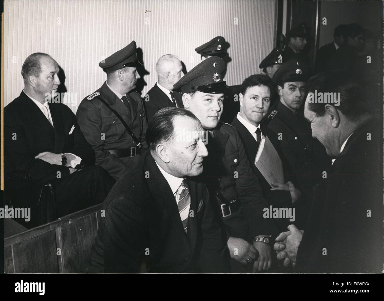 Feb. 02, 1964 - SS Cavalry facing the Law: Five former SS officers of the SS Cavalry Regiment 11 are being tried by the Braun-schweig grand Jury (schwurgericht). today the massacre of jews in the former polish now soviet town of Pinsk, where far behind the front line 5200 Jews were shot to death in August 1941. among the 100 summoned witnesses there is former SS general von dem Bach-Zelewski. Photo Shows Walter Dunsch speaking to his defender, in the last row from L to R: former ''Stumfuhrer'' Hans Walter Zech- Nenntwich, o police officer, and former ''SS obersturmbannfuhrer'' Fanz Magill. - Stock Image
