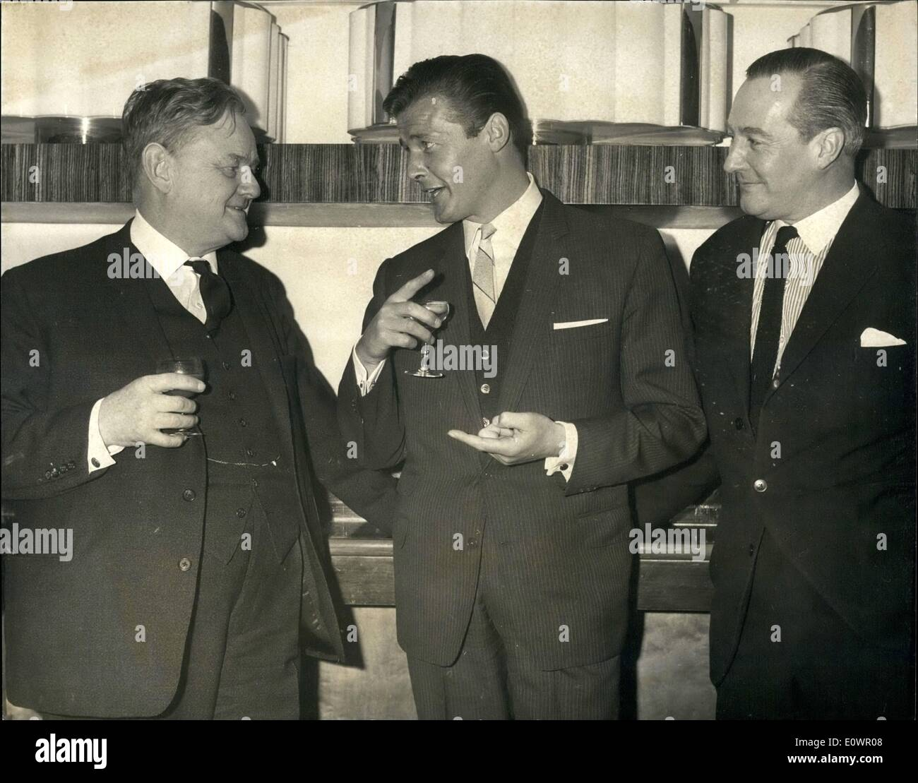 Feb. 02, 1964 - Parliamentarians At Variety Club Luncheon: Distinguished Parliamentarian were Guests of Honor at the Variety Club of Great Britain's luncheon at the Savoy Hotel this morning. Photo Shows (left to right) Mr. Quintin Hogg M.P., Minister of Science, Roger Moore who plays the Saint in the television series, and Mr. Anthony Greenwood M.P. Chairman of the Labor Party, enjoy a drink and a joke together before the luncheon today. - Stock Image