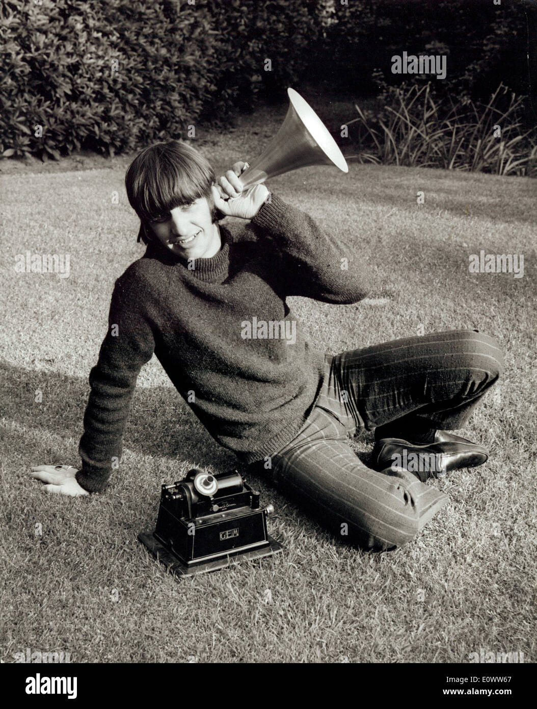 Beatles member Ringo Starr listening to an old megaphone recorder at his home - Stock Image