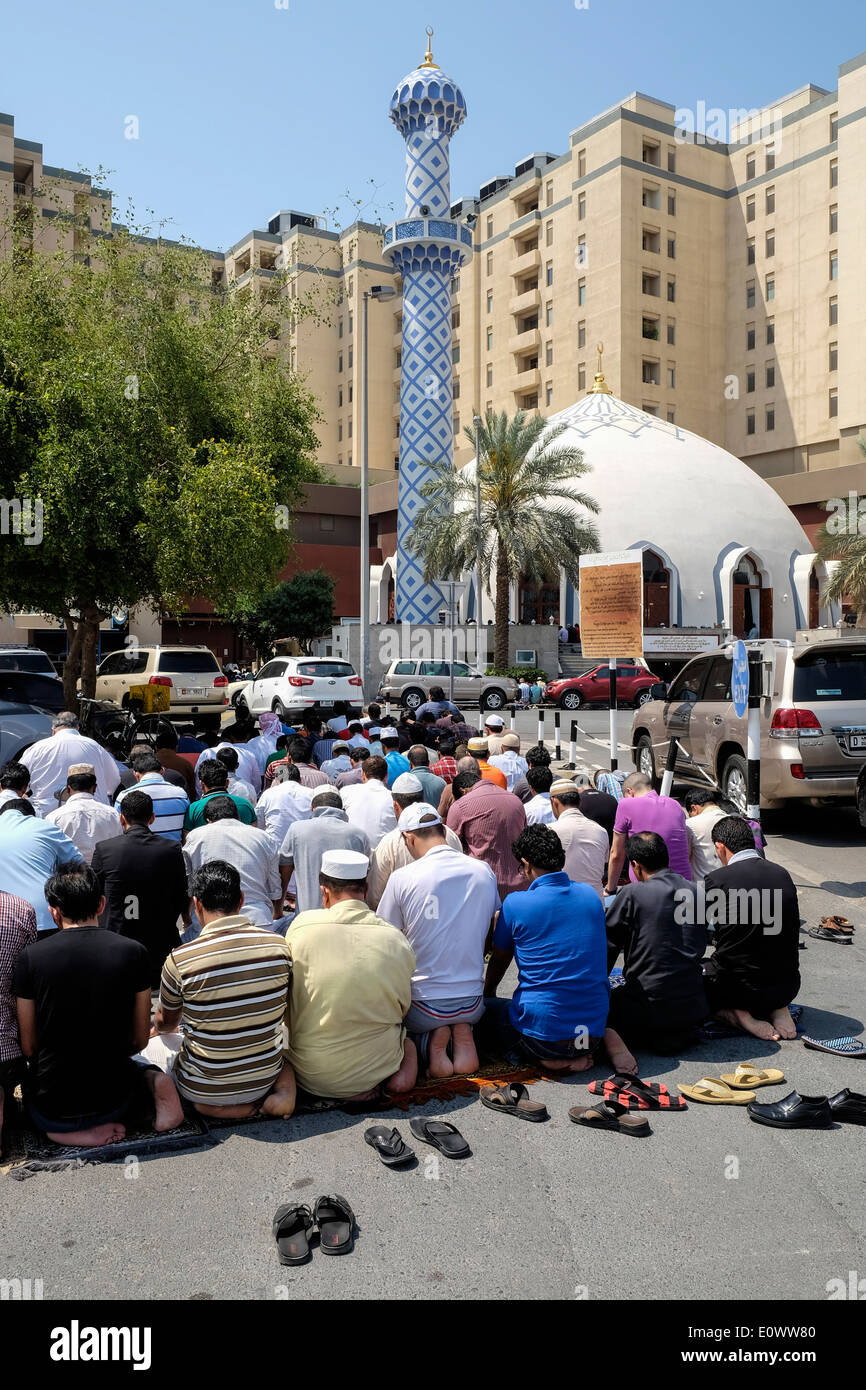 Many men praying on Friday outside mosque at Burjuman shopping centre in Dubai United Arab Emirates - Stock Image