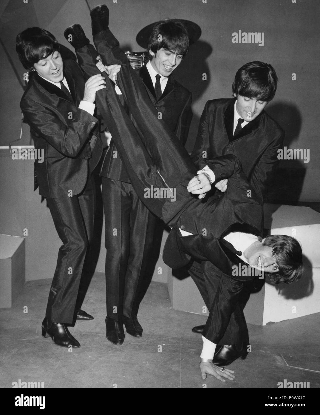 The Beatles members holding Ringo Starr upside down - Stock Image