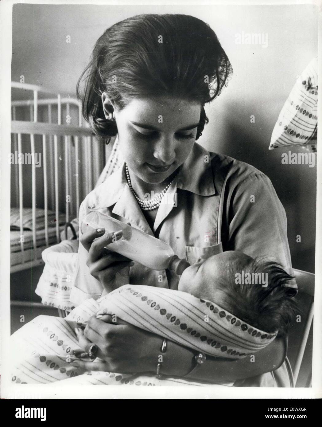 Aug. 06, 1964 - Embargo Until June 12th: Greek Queen-to-be learns child nursery: Princess Anne-Marie, who is engaged to King Constantine of Greece has for some time been learning child nursery at a Copenhagen home for children. Her wedding to the King is due to take place in Athens on September 18th. Photo shows The Princess bottle-feeds a baby. - Stock Image