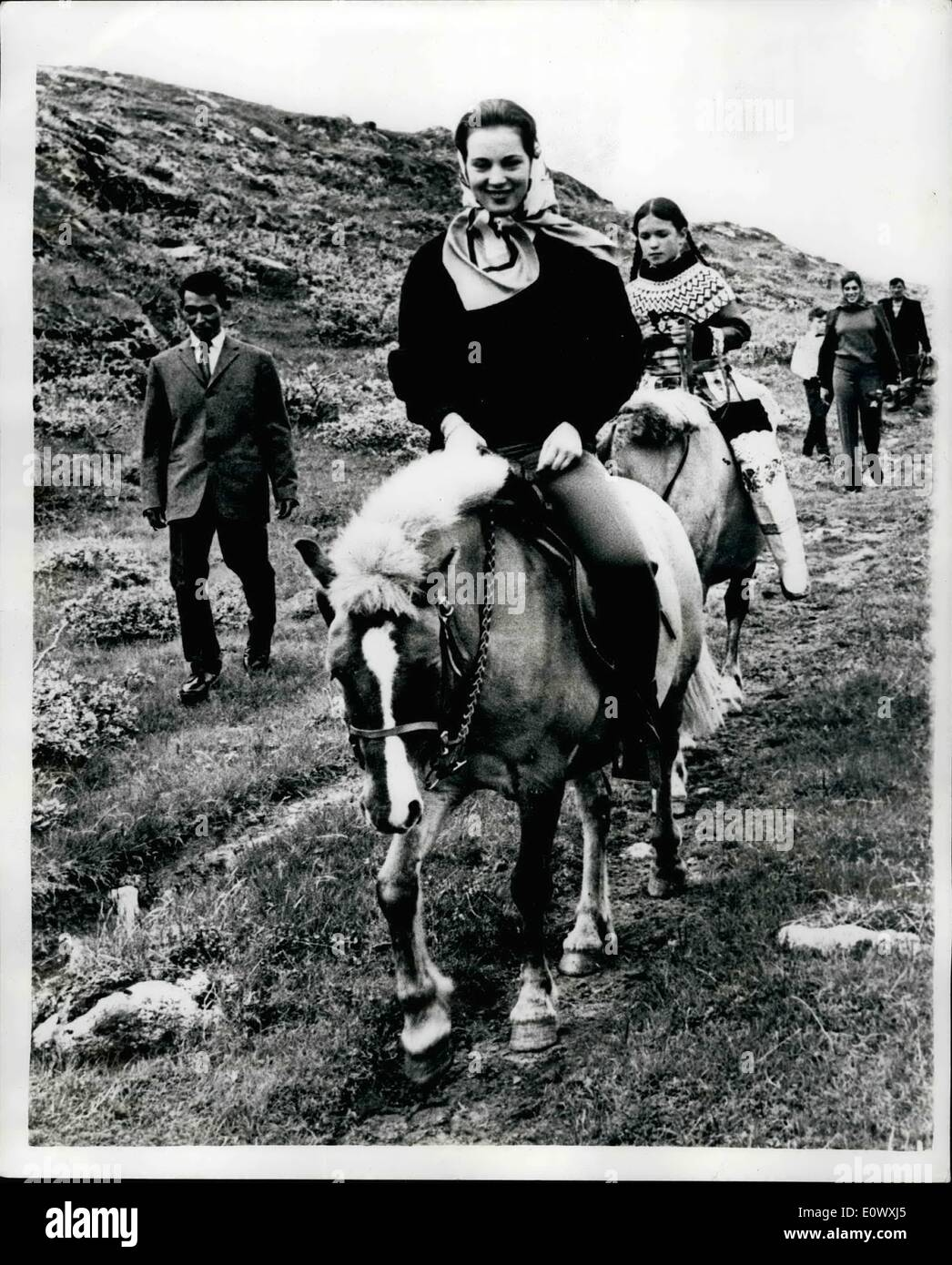 Aug. 08, 1964 - Princess Benedikte Goes Riding - in Greenland... H.R.H. Princess Benedikte of Denmark - is now on visit to Greenland for a tour of the various institutions of the country - children's homes - Red Cross centres etc... Most of her travelling is being done on horse back - owing to the nature of the country side. Keystone Photo Shows: Princess Benedikte during her visit to Quaisartut... Riding behind the Princess is the daughter of the local shepherd. - Stock Image
