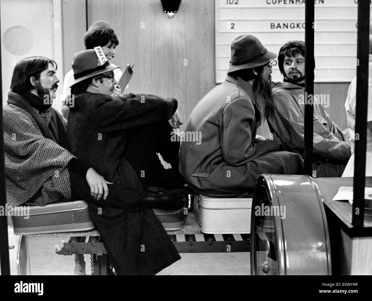 The Beatles riding on the moving luggage band at the airport - Stock Image