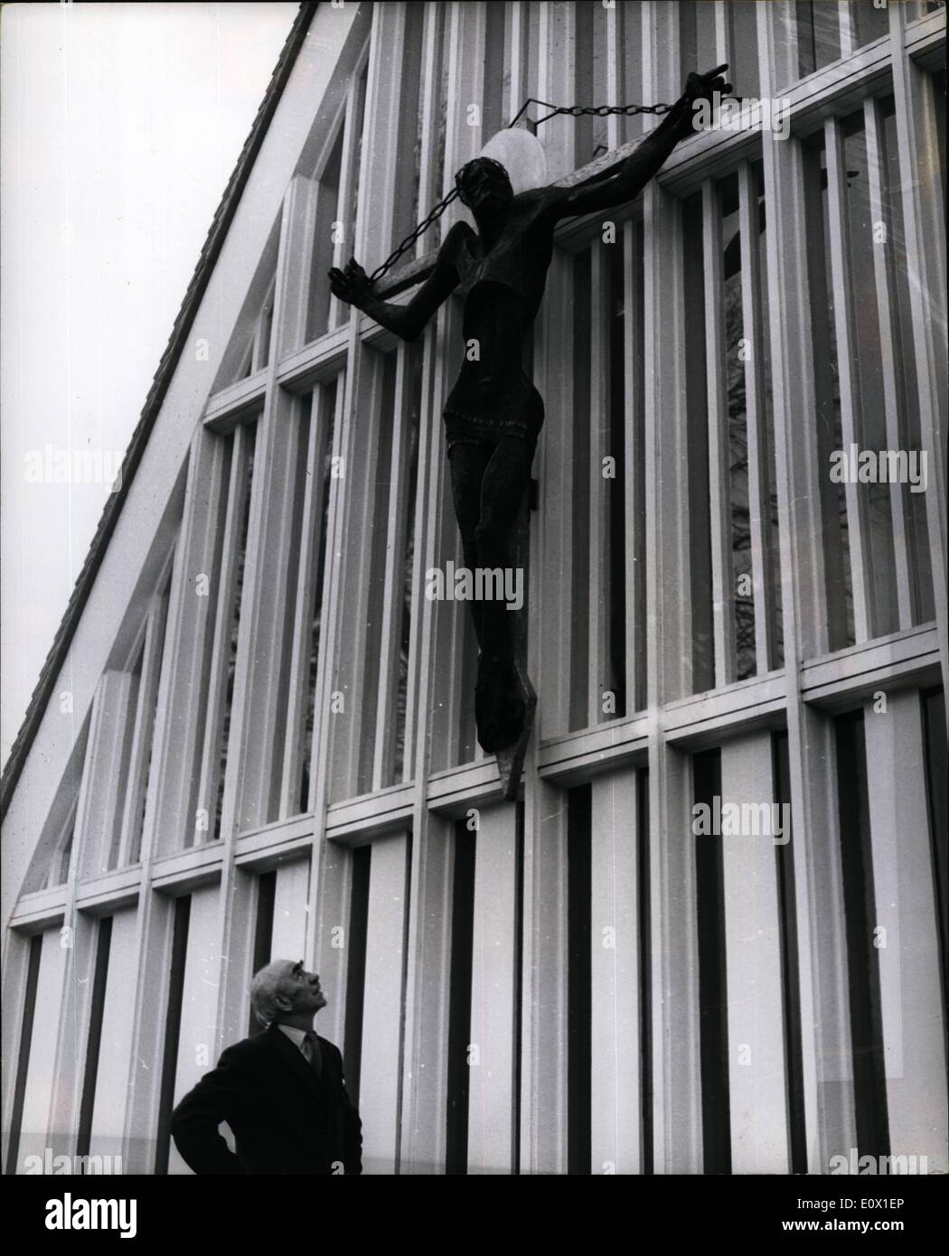 Dec. 12, 1964 - A Figure of Christ carved from Coal-Dust and Fibre Glass is errected on a Sussex Church: A 10-feet high figure of Christ made form coal-dust, mixed with fibre glass - has just been placed into position on the newly built church of St. John, at Broadbridge, near Horsham, Sussex. It is the work of 61-year -old Mr. Bainbridge Copnall, President of the Royal Society of British Sculptors, at his studio near Canterbury, Kent. The figure has already created much controversy and will be a talking point for some time to come Photo shows Mr - Stock Image