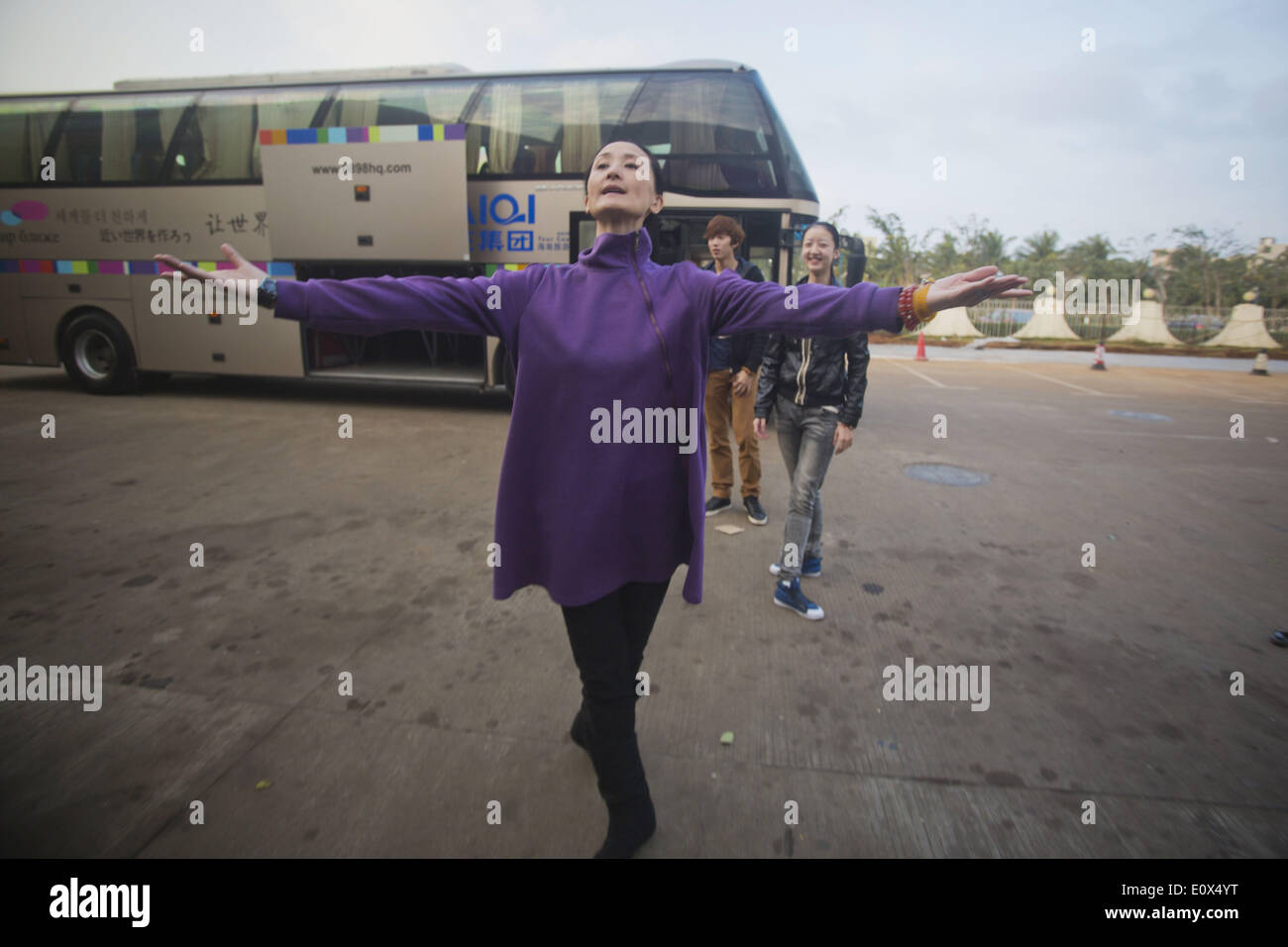 (140520) -- BEIJING, May 20, 2014 (Xinhua) -- Feng Ying, 52-year-old director of the National Ballet of China, demonstrates routines for dancers while they wait for their luggage loaded at Haikou Meilan Airport in Haikou, south China's Hainan Province, Jan. 11, 2014. Before being able to present perfect performance in the spotlight, every member of the National Ballet of China has to undergo severe arduous training for years. Yet they chose to persevere in what they truely love. Years of toiling not only allows them good body shape, expertise and disposition, but also offers them a life-long g - Stock Image