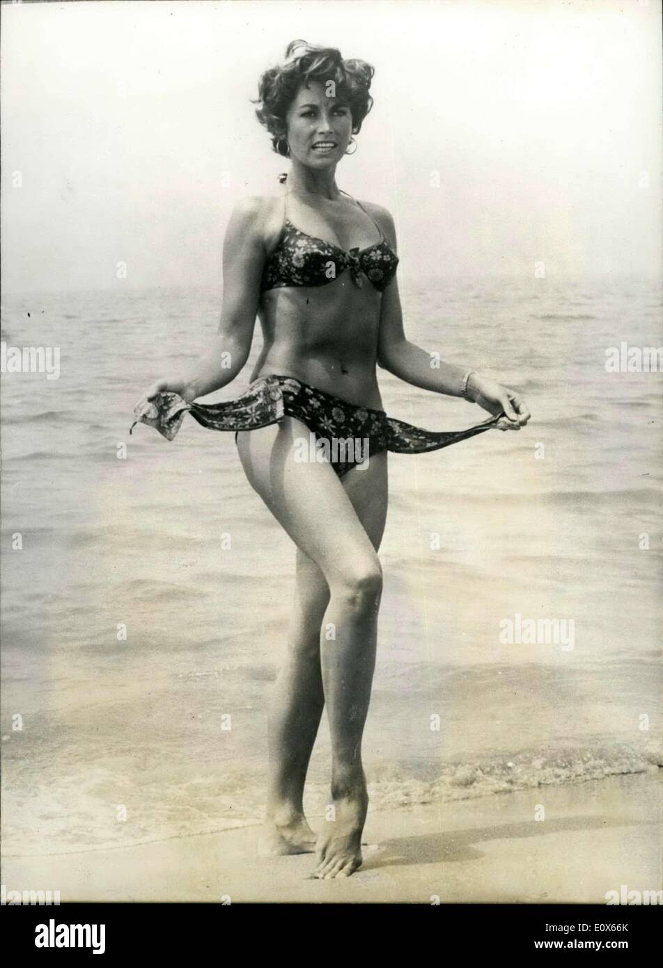 18, 1965 - Bikini - clad Mirelle takes a cooler in the sea