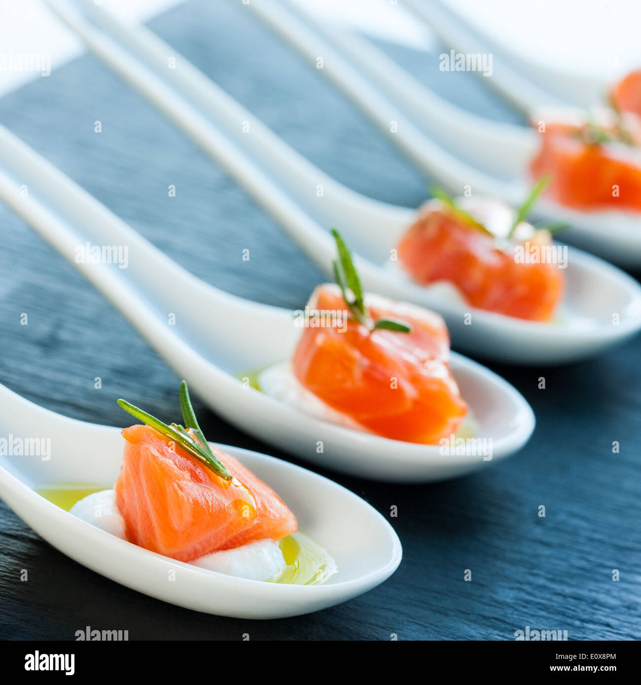 Numerous porcelain spoons with smoked salmon morsels. - Stock Image