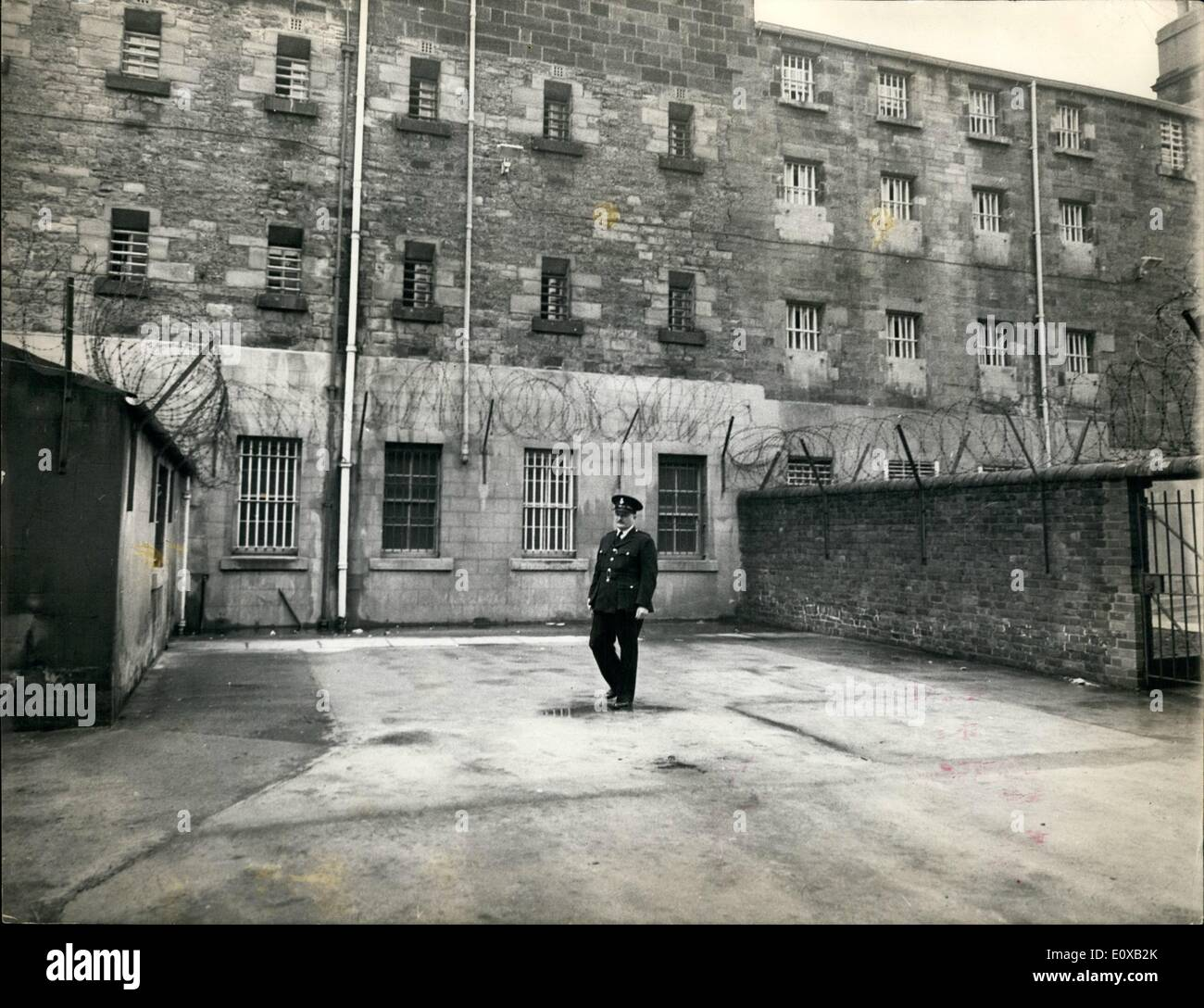 Jan. 01, 1966 - Barbed Wire Walk.: Barbed wire is fixed along walls and to the roof of a building in the exercise yard for prisoners under maximum security at Durham Gaol. The yard is 15-yards by 13-yards. - Stock Image