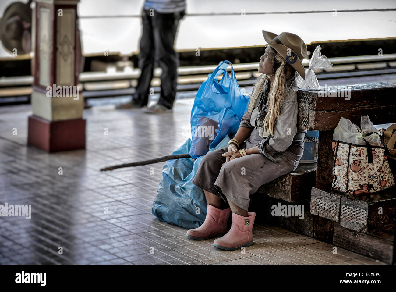 Elderly Thai female traveller waiting at a train station. Thailand S. E. Asia - Stock Image