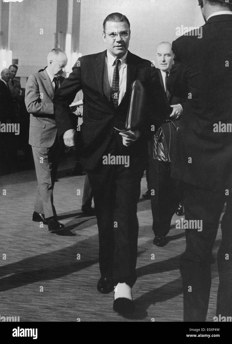ROBERT MCNAMARA, the United States Secretary of Defense, walking with his plastered leg to headquarters, after his accident. - Stock Image