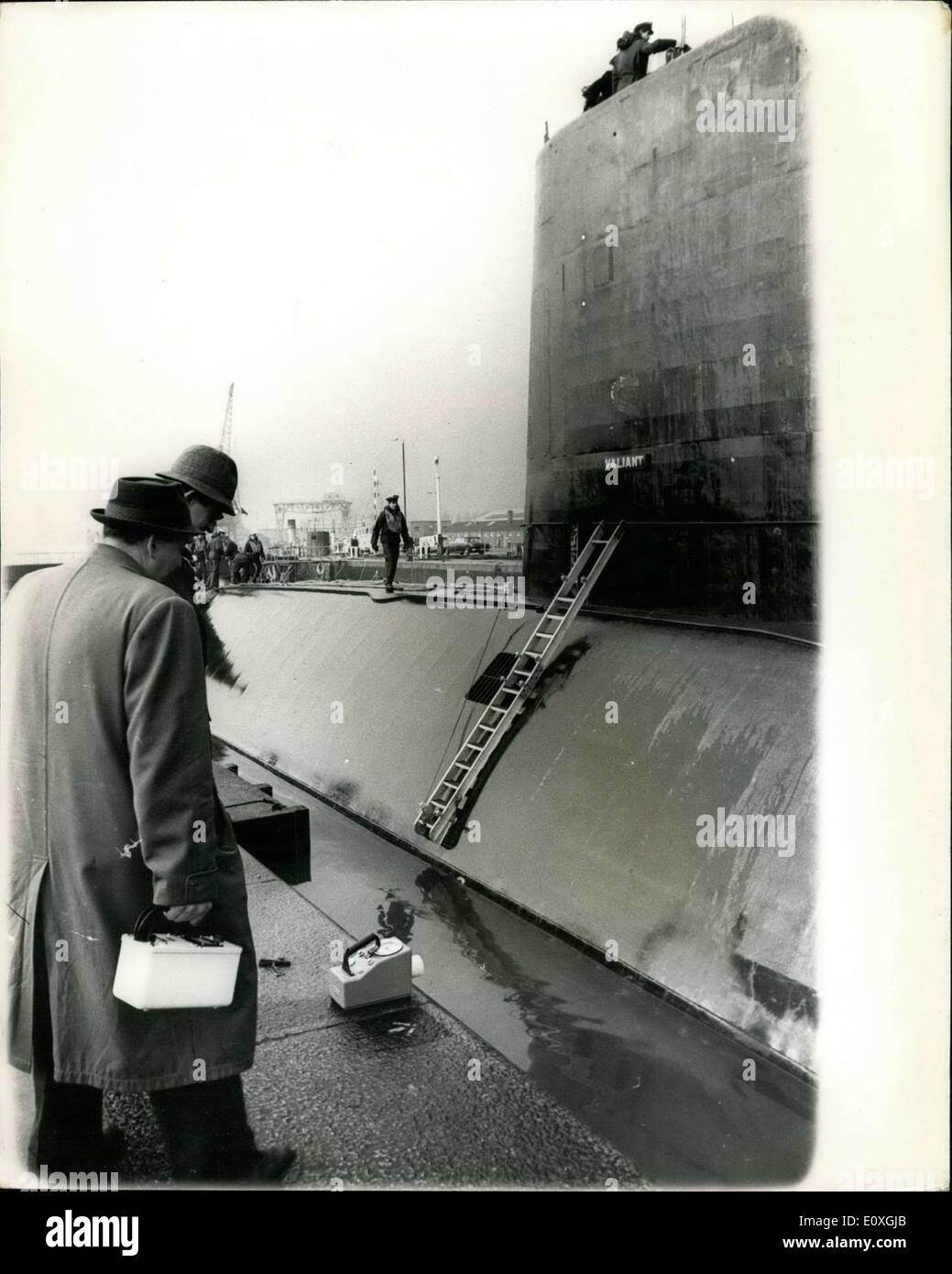 Dec. 12, 1966 - Docking of H.M.S. Valiant at Chatham Chatham dockyard, which is being adapted as refitting and refueling base for nuclear powered submarines, had it first visit from a nuclear submarine, today, when H.M.S. Valiant arrived for routine maintenance and Christmas leave. Keystone Photo Shows: Radiation experts seen with their geiger counters on the dockside carrying out inspection of the immediate area around H.M.S. Valiant, after her arrival at Chatham today. - Stock Image