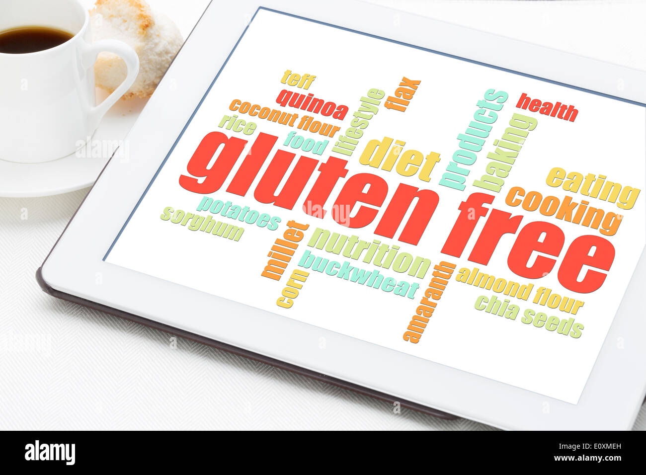 gluten free cooking word cloud on a digital tablet with a cup of coffee - Stock Image
