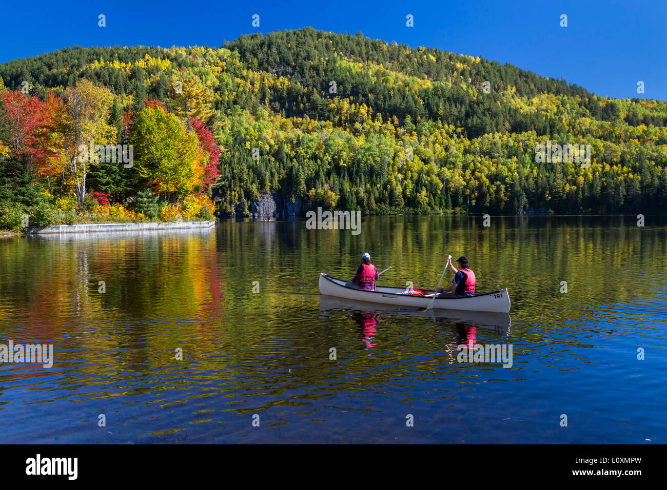Canoing on a lake with fall foliage color in La Maurice National Park, Quebec, Canada. - Stock Image