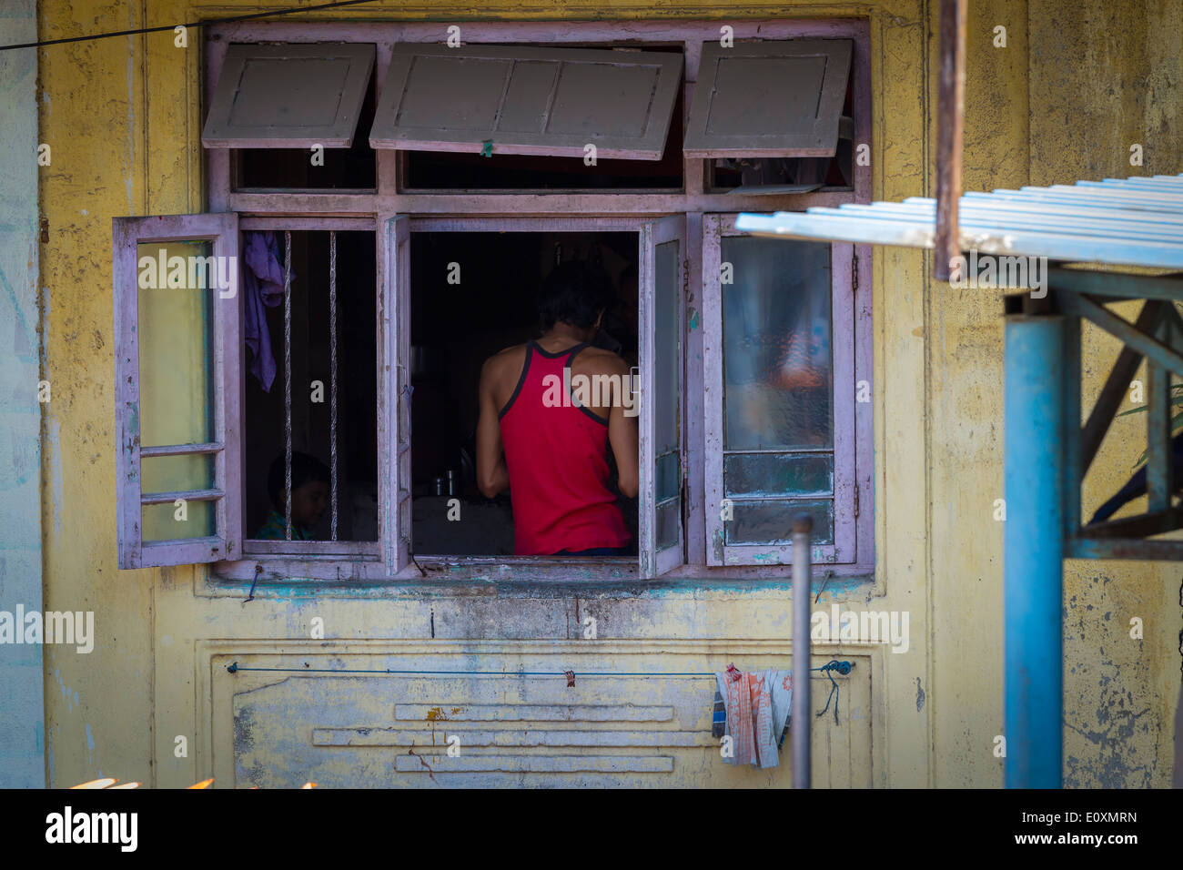 Man stood in a red vest with his back to an open window, Mumbai India - Stock Image
