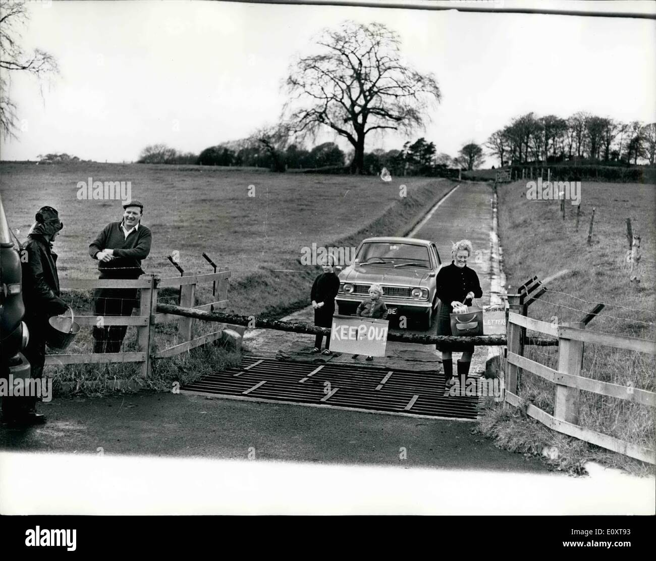 Nov. 11, 1967 - Foot And Mouth Disease Farmer Isolates Family: Farmer Herbert Morris, of Upper Sweeney Farm, Oswestry, has isolated himself and his family inside the boundaries of his farm, to prevent the spread of foot and mouth disease. Photo Shows Former Herbert Morris, in cap, on left, talks over the fence to the milks collection man, whilst his wife, Doreen collects provisions, papers and mail from a collecting box inside the gate, Looking on are the Morris Children, Carol, 2 and Susan, 6. - Stock Image