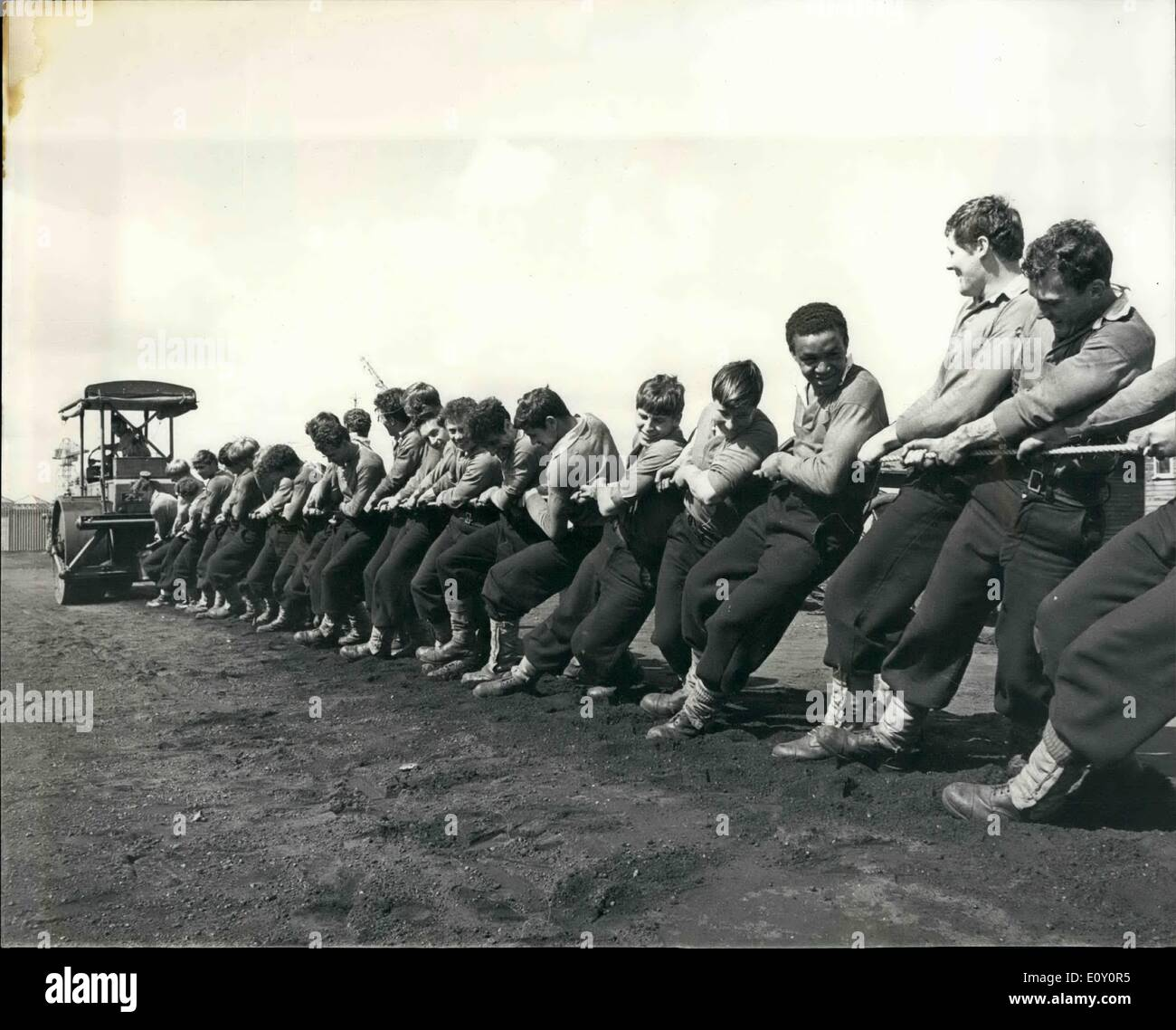 May 05, 1968 - Field gun crew at H.M.S drake take on a ten ton road roller in tug of war match: Devonport field off their week end training session with a tug of war against a ten ton road roller. The roller is kept nearby to roll the training ground after each run, and yesterday after normal training finished the No.1 trainer, P.O (PTI) 'Sandy' Powell, got into the driving seat and challenged the boys. About two dozen tool up the rope and dragged the roller backwards easily (or at least it looked easy) - Stock Image