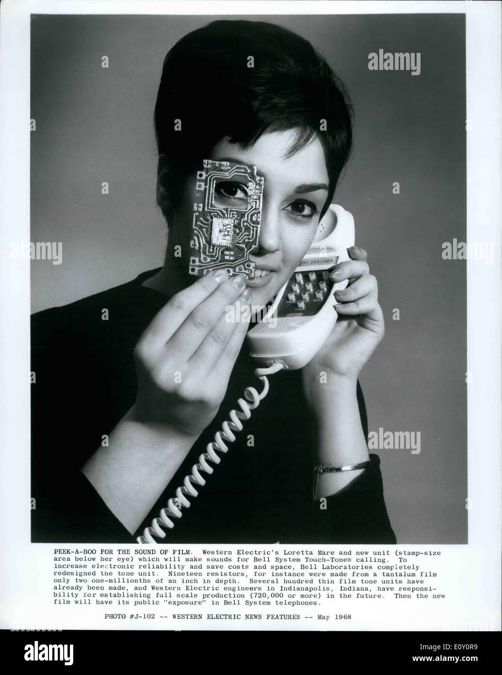 May 05, 1968 - Peek A Boo for the sound of Film. Western Electric's Loretta Mare and new unit (stamp size area below her eye) which will make sounds for Bell System Touch Tones calling. to increase electronic reliability and save costs and space, Bell Laboratories redesigned the tone unit. Nineteen resistors, for instance were made from a tantalum film only two one millionth of an inch in depth - Stock Image