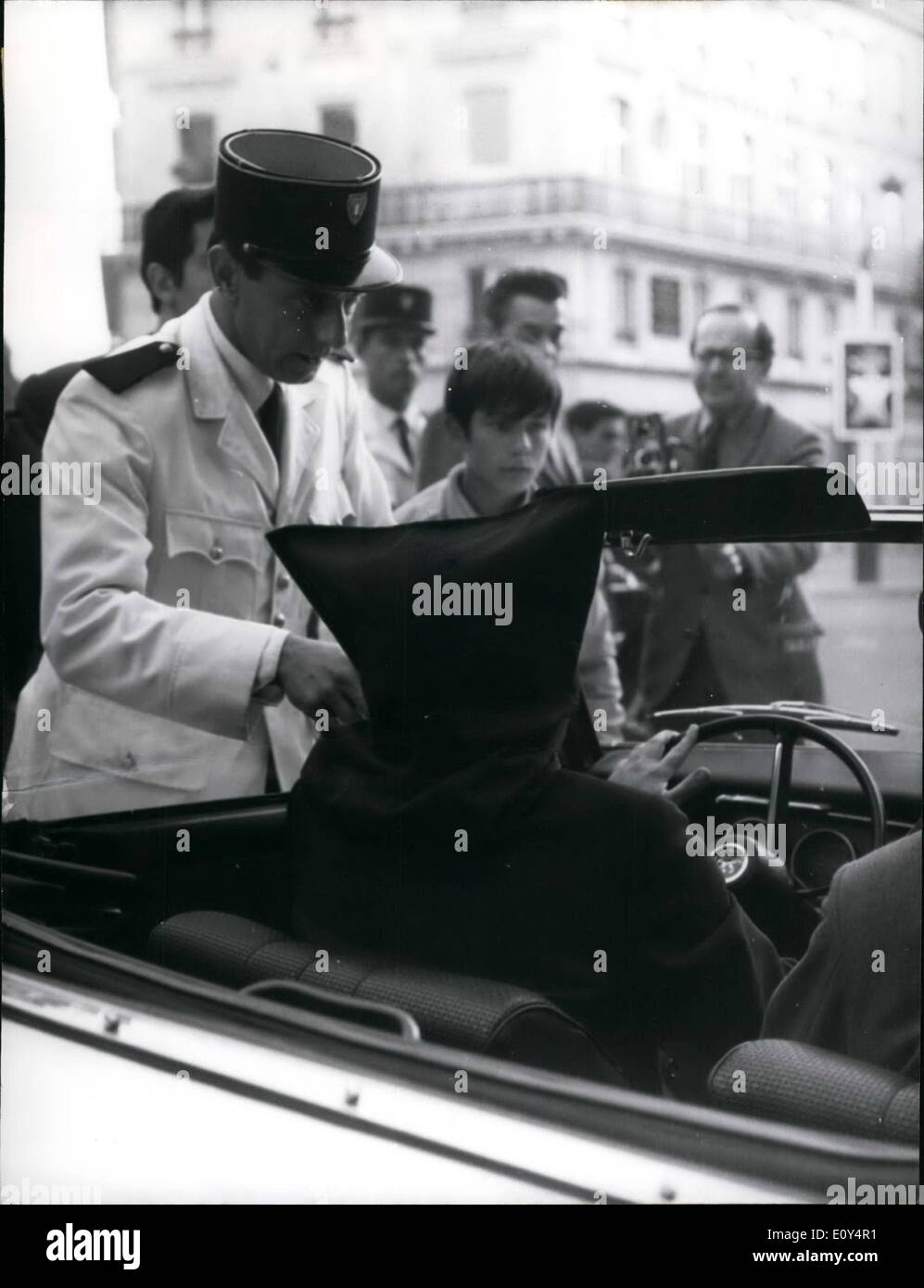 Aug. 08, 1968 - Hooded River Runs Into Traffic Policeman: Paris Traffic Policeman Wearing His White Summer Tunic Seems To Have A Serious Argument With The Black Hooded Driver. To Drive In Paris With Your Eyes Wide Open Is Not Too Easy At All Times. To Drive With A Black Hood On Is Quite A Performance And A Wager Which Dominque Webb Carried Out With Some Success. No Wonder After All As Dominique Webb Is One Of The Magicians And Conjurers Who Will Appear On Olympia's Stage Next Week. - Stock Image