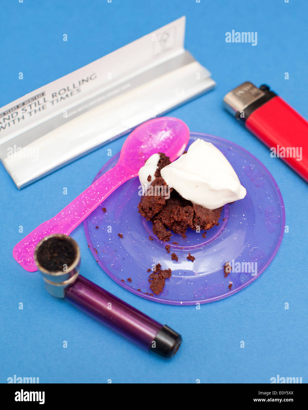 Hash Brownie or Space Cake topped with creme fraiche framed by smoking paraphernalia, London - Stock Image