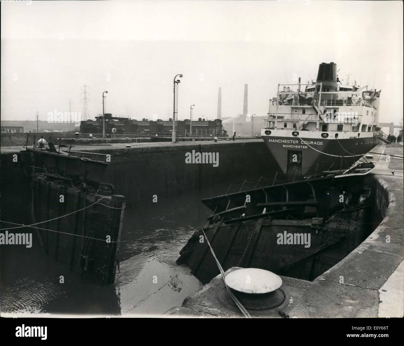 Mar. 03, 1969 - Ship Jammed In Manchester Ship Canal Is Freed: The ''Manchester Courage'', 12,000-ton, which was on her way to Montreal when she rammed giant look gates in the Manchester Ship Canal at Irlam, Lancashire - only eight miles out of Manchester - was freed yesterday, but still lock-bound until the debris of the shattered gates is cleared. The ship was outward bound with a cargo of 400 containers. Until the lock is repaired other ships will not be able to leave or enter the port of Manchester. Photo shows The ''Manchester Courage'' - showing the damaged lock gates in foreground. - Stock Image