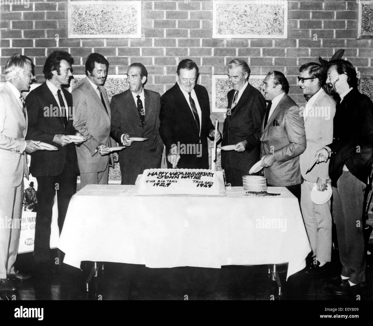 Actor John Wayne cuts his cake surrounded by friends - Stock Image