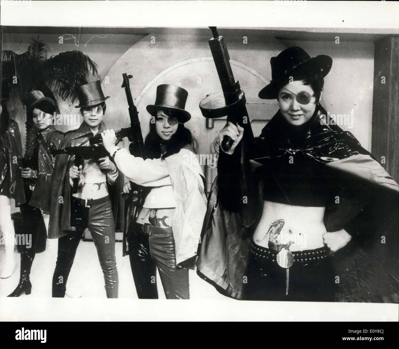Apr. 29, 1969 - Satirical Gangster film made in Japan. Japanese girls wearing coloured plastic capes and pants, transparent covers over one eye, Tommy - guns and a mermaid tattooed on their stomachs, features in new movie named ''Let's Ge. Drifters'' being made in Japan by the Toho film Company. The satirical film underlines the ease in which bank robberies have taken place in Japan recently, one lone robber dressed as a motorcycle the bank employees in the car carrying the cash, that a time bomb was planted beneath the car, and he had been dispatched to warn them - Stock Image