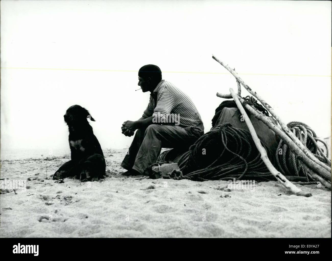 Jun. 19, 1969 - This pair of man and man's best friend are enjoying the morning peace on a beach in the south of France. The area was populated by tourists during this time. - Stock Image