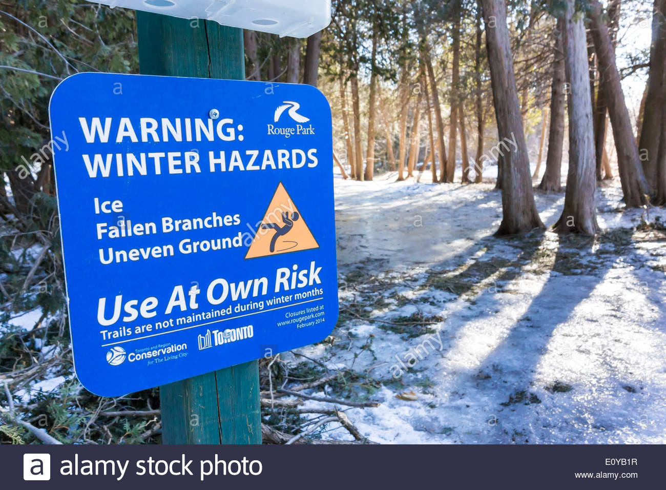 Trail sign warning of winter hazards in Rouge National Urban Park an urban wilderness inside Toronto Ontario Canada - Stock Image