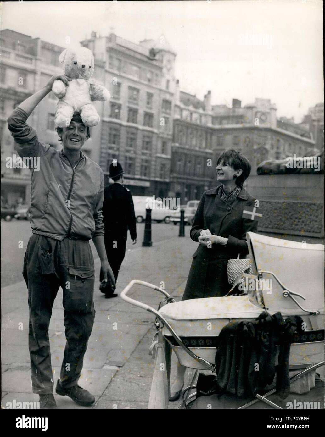 Aug. 08, 1969 - Pram Pusher Arrives At Trafalgar Square From Sweden; 23 year old bachelor, Mr. Lennart Jonsson, arrived at Trafalgar Square today, after having tramped 1,370 miles in 40 days fro stacknels, pushing a  The pram, and a teddy bear are presents for Mrs. Gail Fonelon. 24 of Lawastaft, who is expecting a baby anyday now. He stayed with her mother, Mrs. Constance Lamble of James Lane, Burgess Will, Sessex, When studying in Brighten in 1964-65. She was at Trafalgar Square to greet him. Photo Shows Mr. Lenmart Jonsson hands over the pram and teddy bear to Mrs - Stock Image