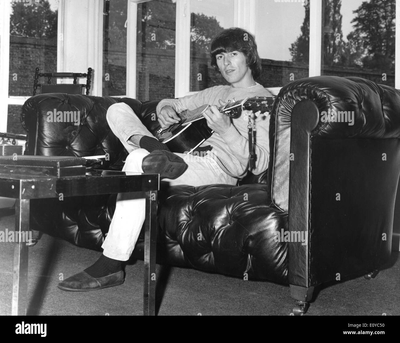 The Beatles George Harrison plays guitar on couch Stock Photo