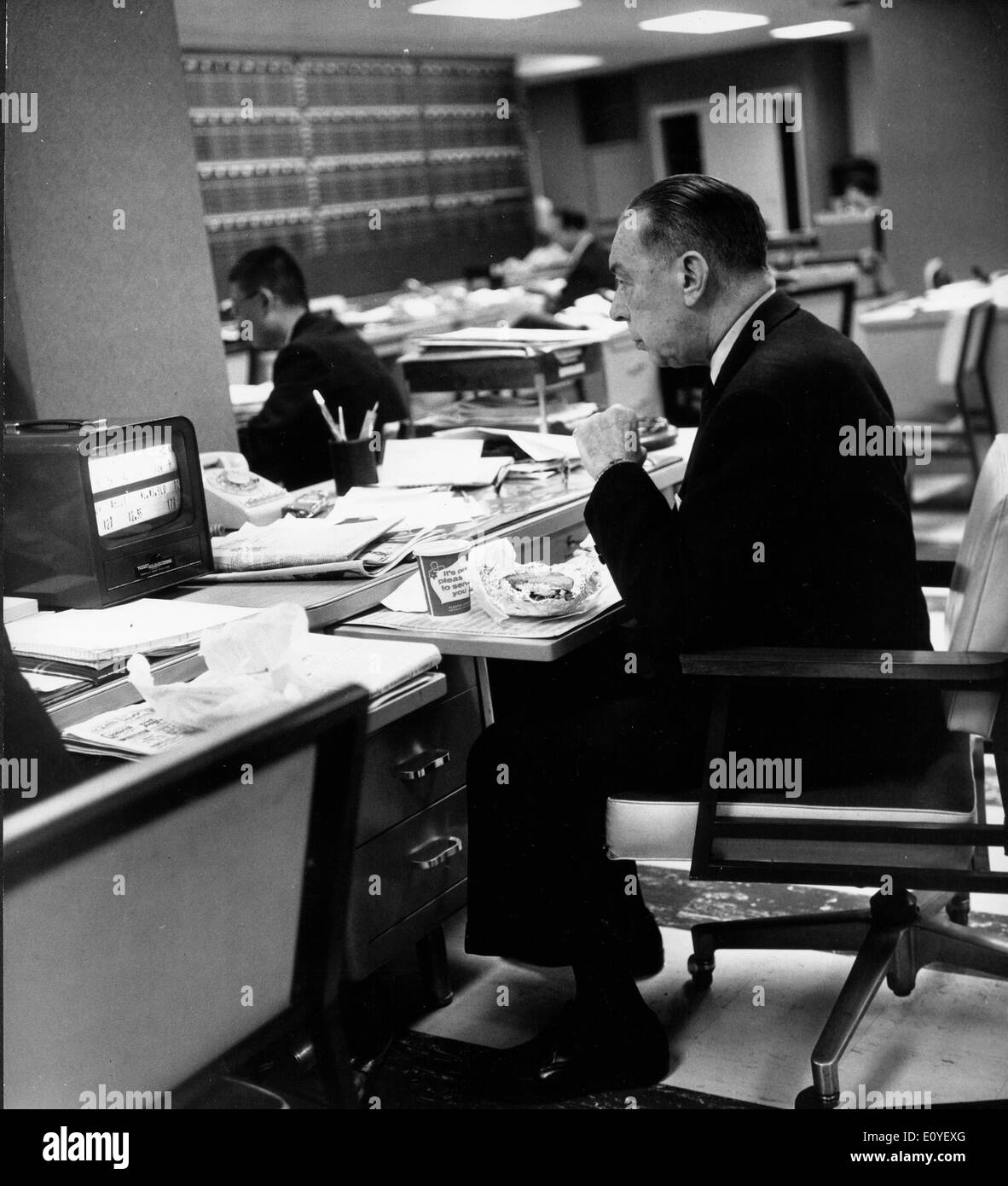 Jan. 01, 1970 - New York, New York, U.S. - File Photo: circa 1970s. A man eats lunch while working at Goodbody and Co., one of the largest investment firms in the U.S. - Stock Image