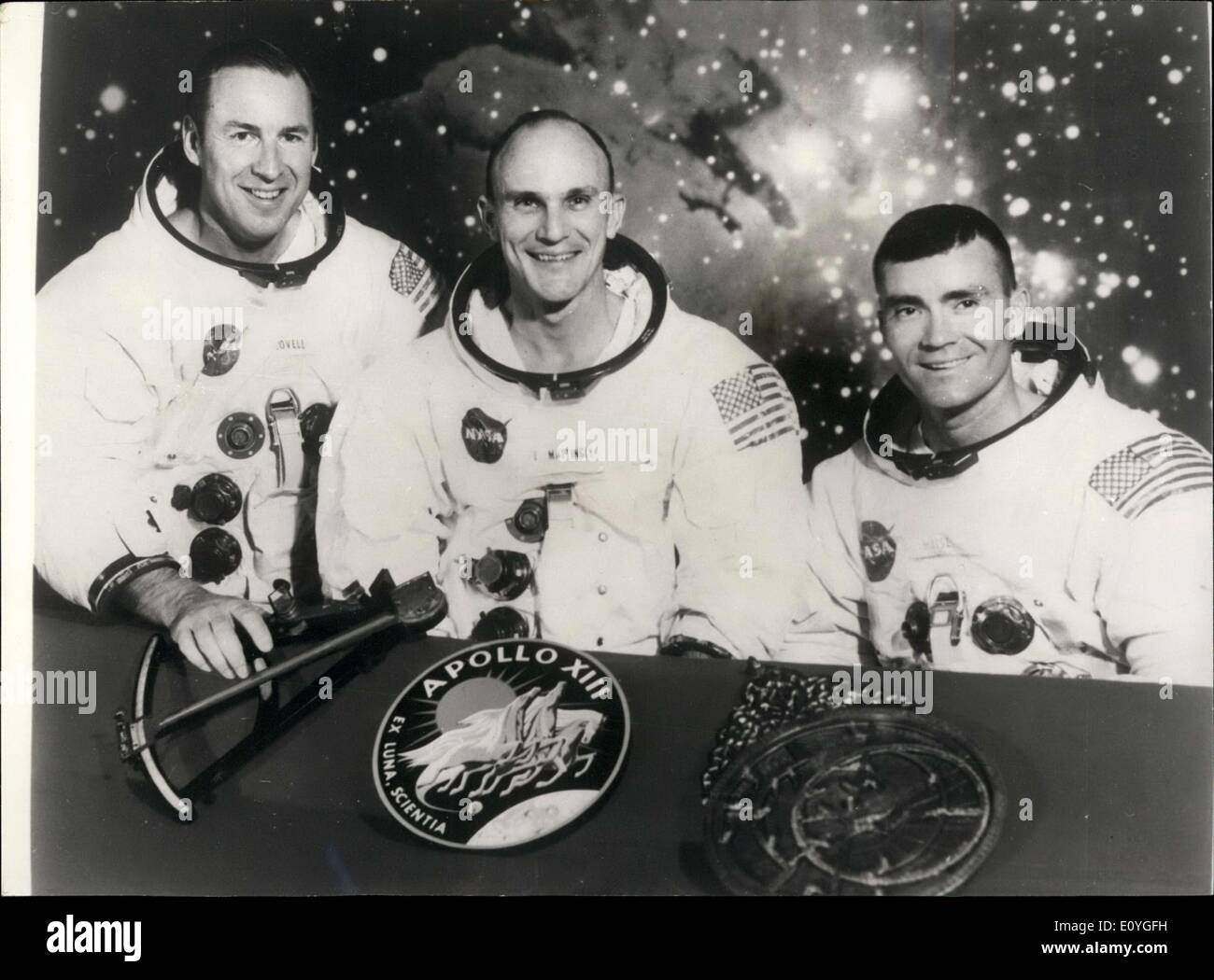 Apr. 11, 1970 - Seventh manned Apollo crew: The members of the prime crew of the Apollo 13 lunar landing mission are (l to r), Astronauts James A. Lovell; Thomas K. Mattingly, and Fred W. Haise. they are seated in front of a scene of the Lagoon Nebula, with the mission insignia and two items of early navigation in the foreground. Represented in the Apollo 14 emblem (center) is Apollo, the sun god of Greek mythology, symbolizing that the Apollo flights have extended the light of knowledge to all mankind - Stock Image