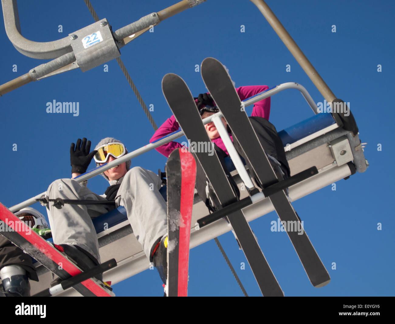 Skiers on a ski lift - Stock Image